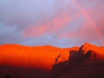 Regenbogen über rotem Berg Stockbild