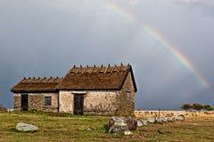 Regenbogen über schwedischem altem Haus Stockbilder