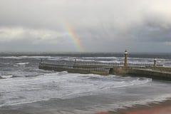 Regenbogen über Whitby Hafenpiers. Stockbild