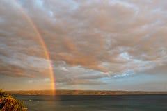 Regenbogen auf dem Himmel über dem Meer Stockbild