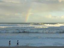 Regenbogen über rauem Meer Stockbild