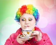 Regenbogen-Clown mit Tasse Tee lizenzfreie stockfotografie