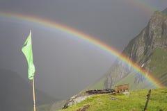 Regenbogen, der über ein Gebirgstal vor dunklem Gewitter ausdehnt Stockfotos