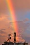 Regenbogen, der für Telekommunikationsantenne fällt Stockbild