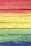 Regenbogen-Farben gemalt auf verwittertem Holz Stockfotografie
