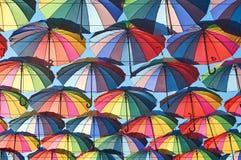Regenbogen farbige Regenschirme über der Straße Stockfotografie