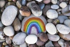 Regenbogen gemalt auf Kiesel mit Steinhintergrund Lizenzfreies Stockbild