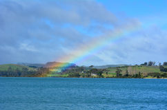 Regenbogen im Himmel und über dem Meer Lizenzfreie Stockfotos