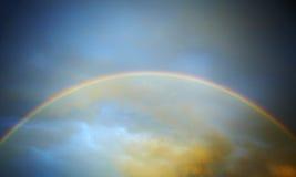Regenbogen infront des Sonnenunterganghimmels Stockfotografie