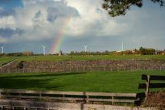 Regenbogen mit Windmühlen in der niederländischen Landschaft lizenzfreie stockfotografie