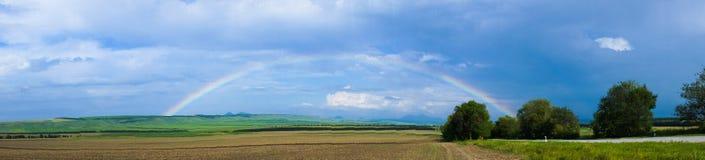 Regenbogen mit Wolken über Bauernhoffeld Stockfotos