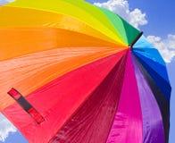 Regenbogen-Regenschirm gegen den Himmel Lizenzfreies Stockbild