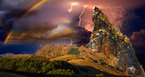 Regenbogen und Blitz über dem Felsen Stockfoto