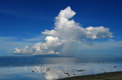 Regenbogen und Gewitter über einer tropischen Insel. Lizenzfreies Stockfoto