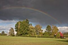 Regenbogen und Regen über einem Feld Lizenzfreie Stockfotos