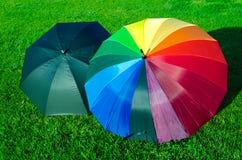 Regenbogen und schwarze Regenschirme auf dem Gras Lizenzfreie Stockfotos