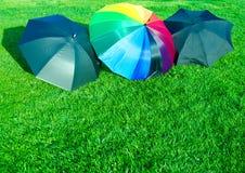 Regenbogen und schwarze Regenschirme auf dem Gras Stockbild