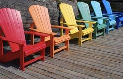 Regenbogen von farbigen Stühlen auf dem Dock im Sommer Lizenzfreie Stockfotografie