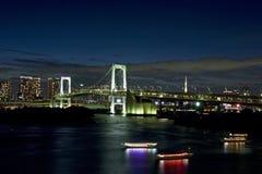 Regenbogenbrücke und -tokyo ragen nachts hoch Stockfoto