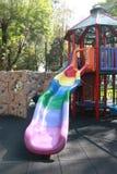 Regenbogendia auf dem Spielplatz Stockbilder