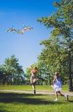Regenbogendrachen im Himmel Zwei Mädchen, die mit Drachen spielen und laufen Stockfotos