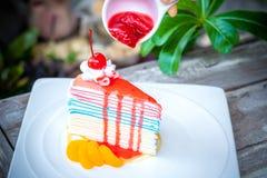 Regenbogenkreppkuchen und eine Kirsche stockfoto