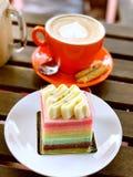 Regenbogenkuchen mit Latte Genießen des hohen Tees Stockbild