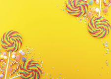 Regenbogenlutschersüßigkeit auf heller gelber hölzerner Tabelle Stockfotografie