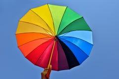 Regenbogenregenschirm auf blauem Himmel Lizenzfreie Stockfotos