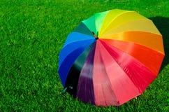 Regenbogenregenschirm auf dem Gras Stockfoto