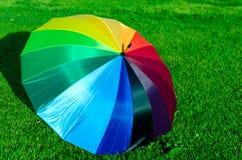 Regenbogenregenschirm auf dem Gras Lizenzfreies Stockfoto