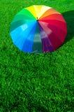 Regenbogenregenschirm auf dem Gras Lizenzfreie Stockfotos