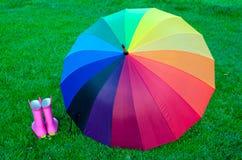 Regenbogenregenschirm mit Stiefeln auf dem Gras Stockbilder