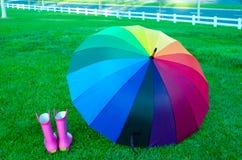 Regenbogenregenschirm mit Stiefeln auf dem Gras Stockfotos