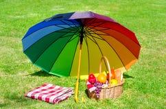 Regenbogenregenschirm und Picknickkorb Stockfotografie