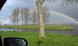Regenboog buiten het autoraam Stock Foto