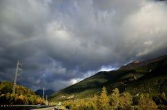 Regenboog in de bergen met zeer donkere hemel stock foto's