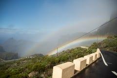 Regenboog in de bergen naast een bergweg Royalty-vrije Stock Fotografie
