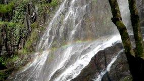 Regenboog in de waterval op de achtergrond van groene rotsen stock video