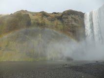 Regenboog door mist wordt gecreeerd die uit de waterval van Skà ³ gafoss, IJsland komen dat royalty-vrije stock foto's