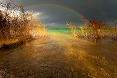 Regenboog en donkere wolken over groot meer Royalty-vrije Stock Afbeeldingen