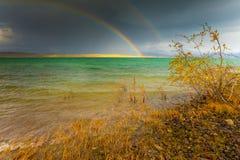 Regenboog en donkere wolken over groot meer Royalty-vrije Stock Foto