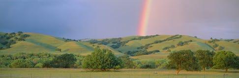 Regenboog en rollende heuvels i Stock Foto
