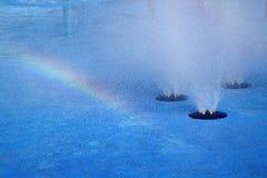 Regenboog en waterfonteinachtergrond Stock Foto's