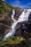 Regenboog en waterval in de bergenvallei in Noorwegen Stock Foto