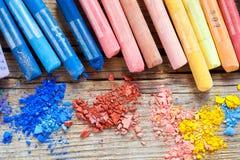 Regenboog gekleurde pastelkleurkleurpotloden met verpletterde krijtclose-up op des Stock Foto's