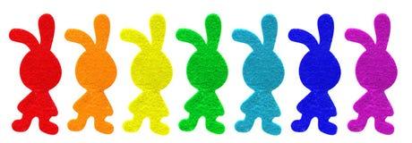 Regenboog geschilderde gevoelde Pasen-konijntjes Stock Foto's