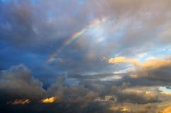 Regenboog na de regen op de achtergrond van onweerswolken Stock Foto's