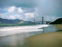 Regenboog naast golden gate bridge weg van het strand met regenwolken en bergen op de achtergrond stock foto's