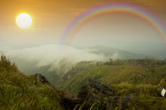 Regenboog op nevelige berg in het regenachtige seizoen Stock Afbeeldingen
